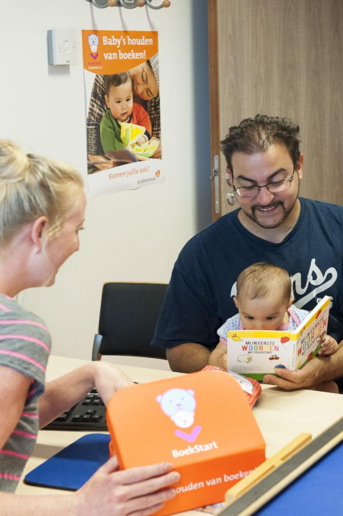 Vader met baby op consultatiebureau, BoekStartkoffer wordt uitgereikt