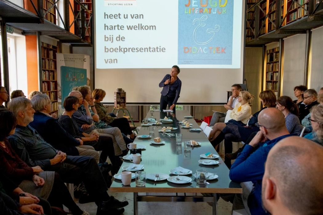 Tafel met aanwezigen eromheen. Gerlien van Dalen start presentatie aan het hoofd van de tafel, met op de achtergrond een powerpointpresentatie.