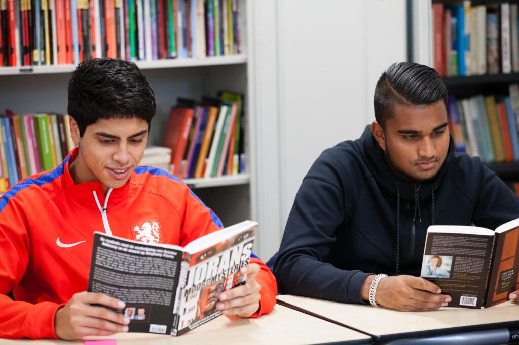 Twee mbo-studenten lezend aan hun tafeltjes in een lokaal met boekenkast op de achtergrond