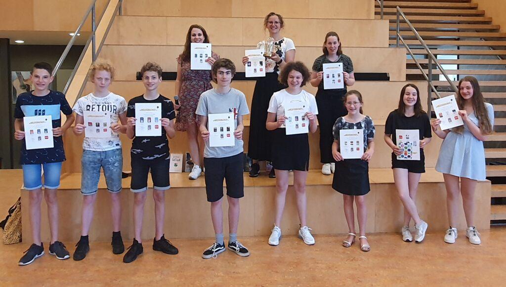 Groepsfoto winnaars De Weddenschap, leerlingen staan voor en op trap met oorkonde,